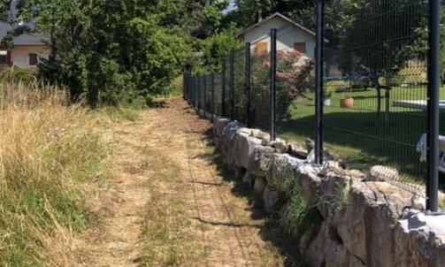 Pose d'une  d'une clôture sur un enrochement